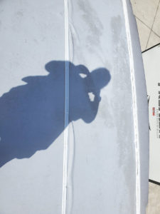 rv roof with wrinkles and shadow of person taking picture